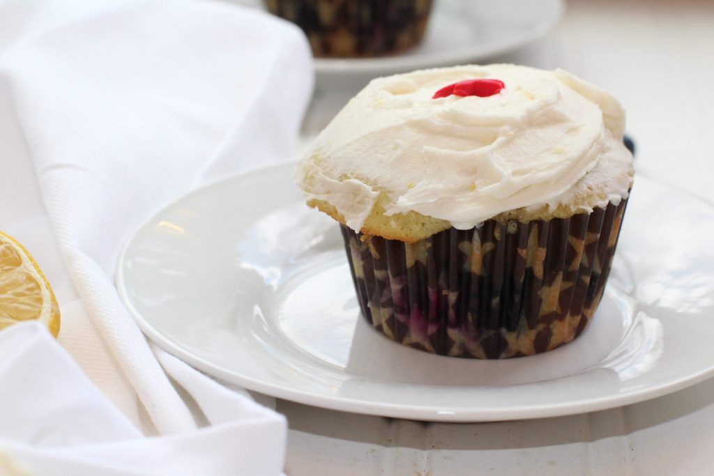 blueberry cupcake on plate with napkin lemon frosting