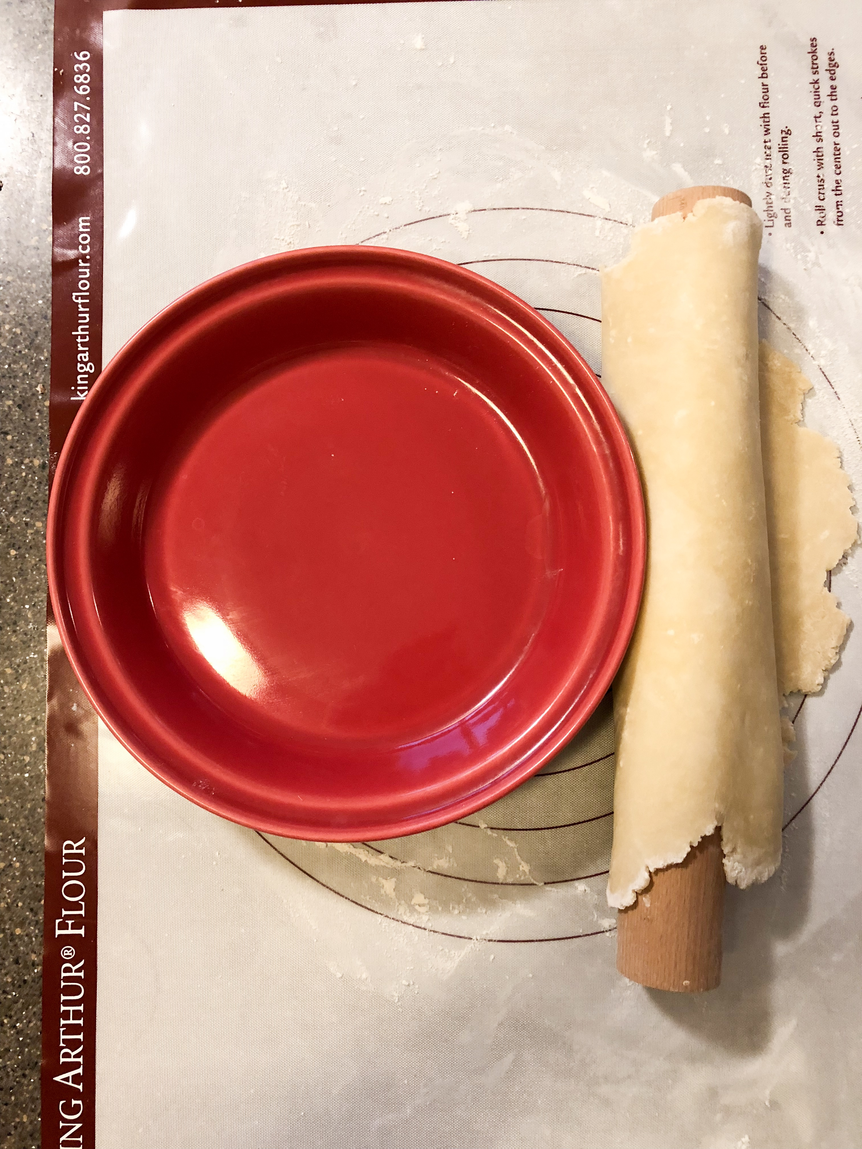 pie crust over rolling pin with red pie pan