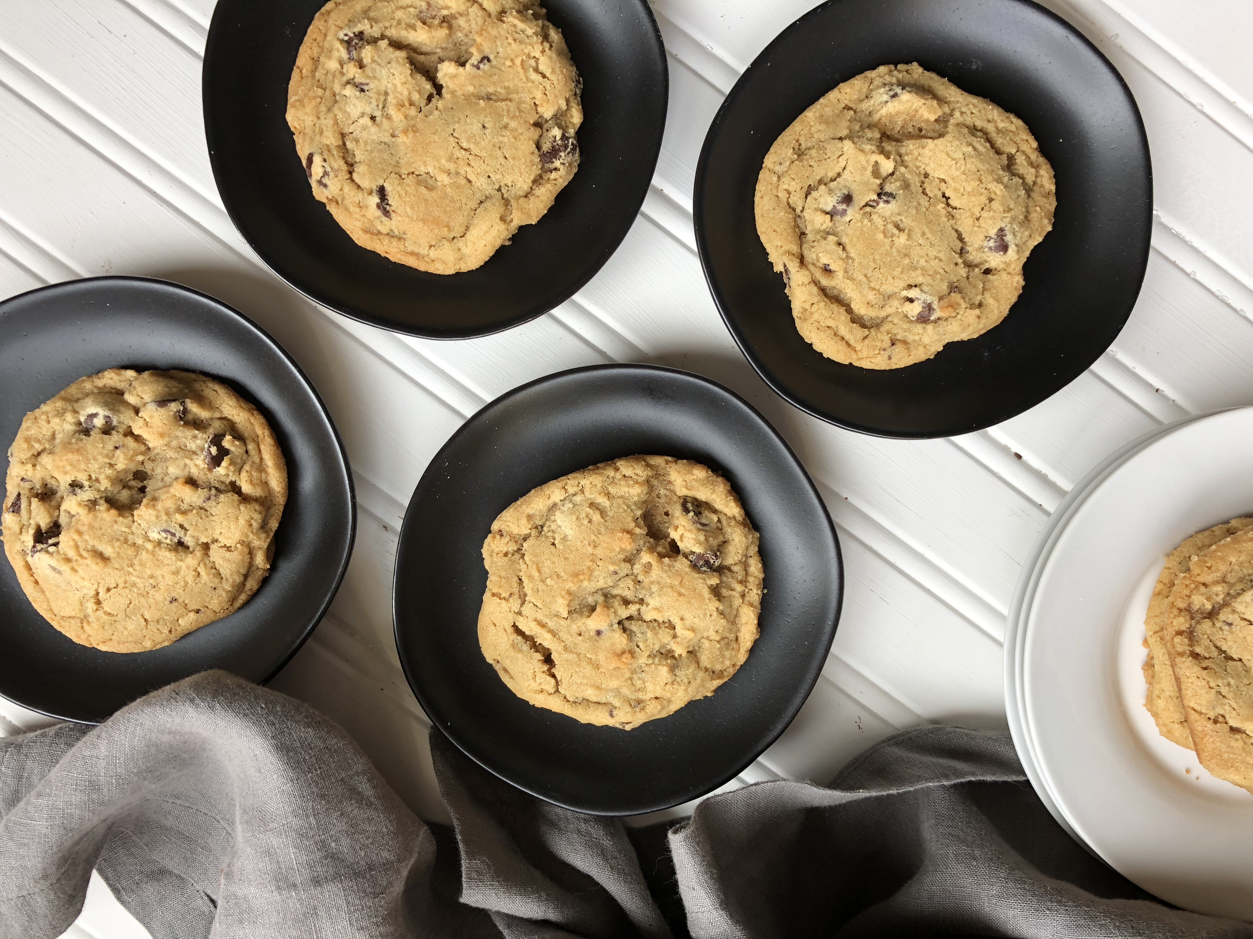 chocolate chip cookies on black plates with napkin