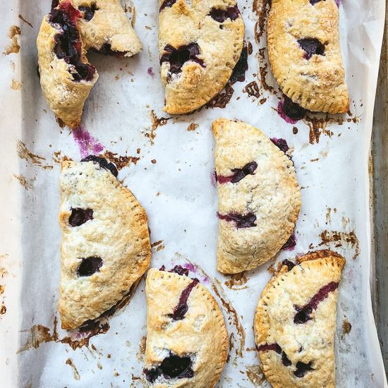 blueberry apple turnovers overhead on cookie sheet