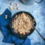 pear apple cranberry crisp overhead with spoon napkin and hazelnuts
