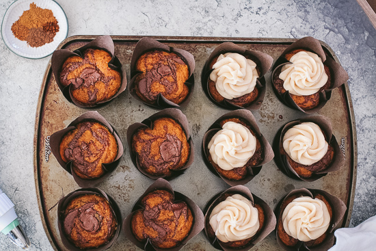 pumpkin nutella cupcakes overhead in pan half frosted