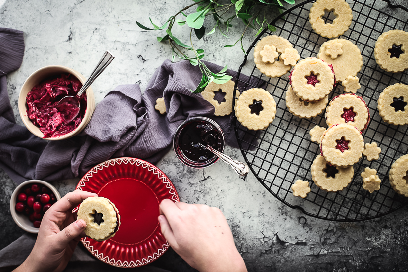 linzer cookies spreading jam with red plate